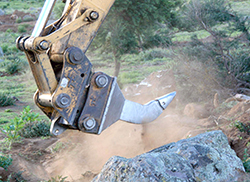 Ripper attached to a bulldozer digging into brown earth