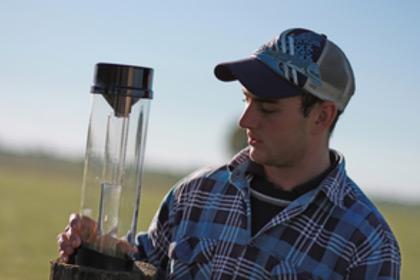 A young farmer checks a rain gauge.